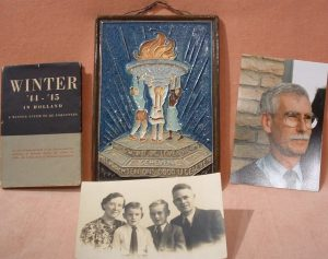 4 items,a book, a clourful ceramic plaque, a colur photo of a man and a sepia photograph of a family