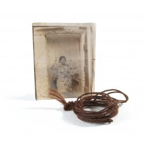 a coil of rope made from brown hair accompanied by a sepia photo of a woman using the rope as a swing